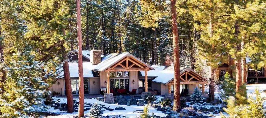 Trinity Building Systems Ozark Model Home with Logs covered in snow.
