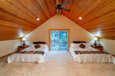 Trinity Building Systems prefabricated mountain home guest room with two beds.